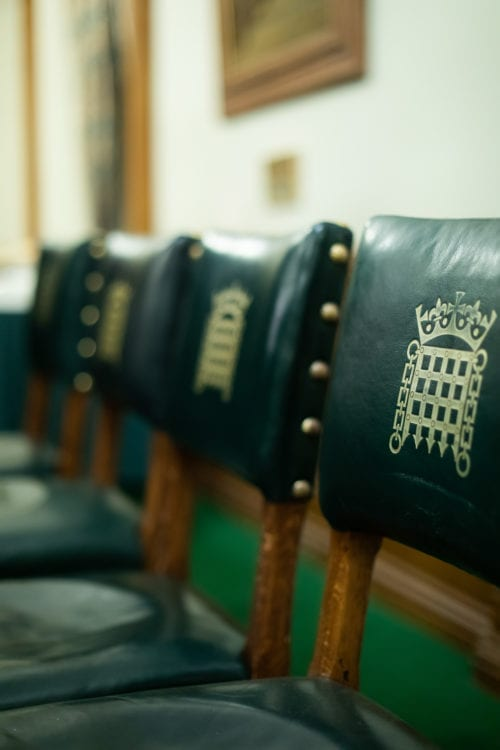 A row of green padded chairs with the Portcullis House/APPG logo on each chair. The first chair is in focus and the rest of the chairs in the row are blurred.