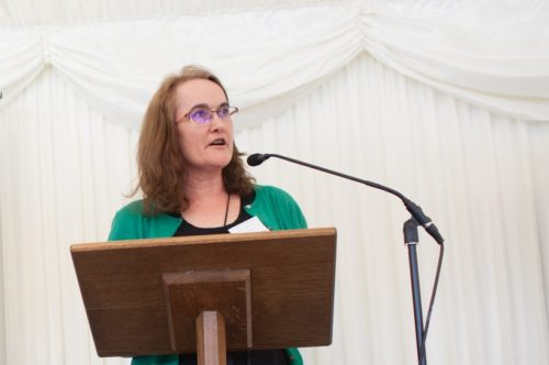 Image shows Fiona speaking at an event. She is standing behind a lectern wearing a green cardigan and black top.