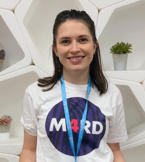 Headshot of a woman wearing a blue lanyard and a white t-shirt with a purple circle and 'M4RD' in the middle of the circle. The '4' is in pink and the other letters in white.