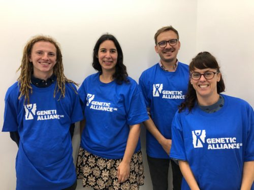 Two male and two female members of the Genetic Alliance UK team stand in front of a white wall. All wearing large blue t shirts branded with the Genet Alliance UK logo